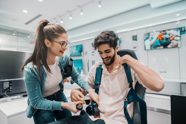 Coppie multiculturali sorridenti che provano tecnologia di realtà virtuale. uomo seduto in poltrona mentre donna allacciata cintura. interno del negozio di tecnologia.