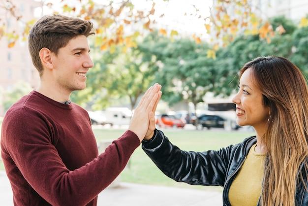 Coppie multietniche che danno il livello cinque e che sorridono