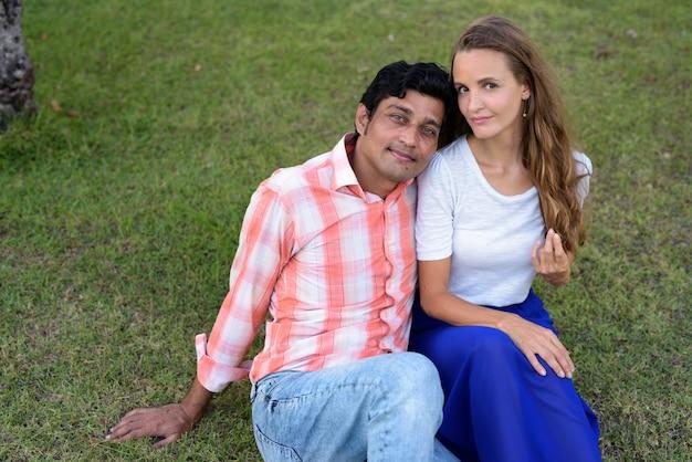 Coppie multietniche che si siedono sul prato nell'amore
