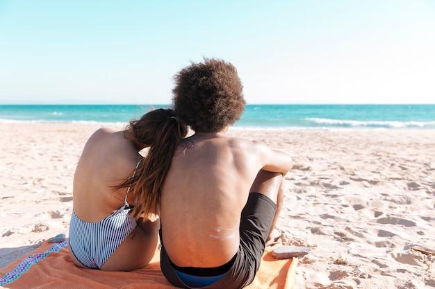 Coppie multietniche che si siedono sulla spiaggia