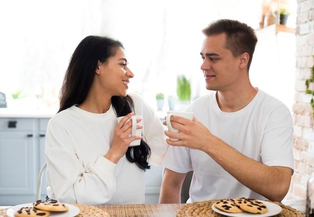 Coppie multirazziali che bevono dalla tazza a casa