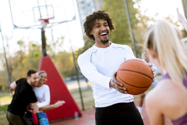 Coppie multirazziali che giocano pallacanestro sulla corte all'aperto