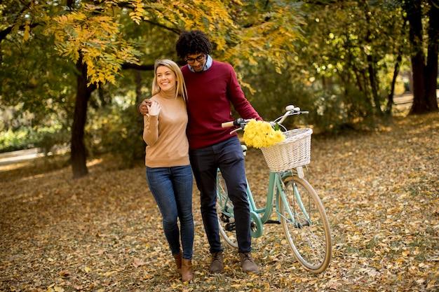 Coppie multirazziali con la bicicletta che camminano nel parco di autunno