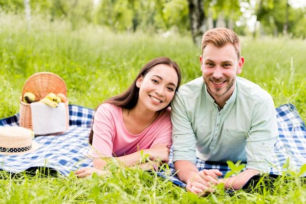 Coppie multirazziali sorridenti che posano sul picnic