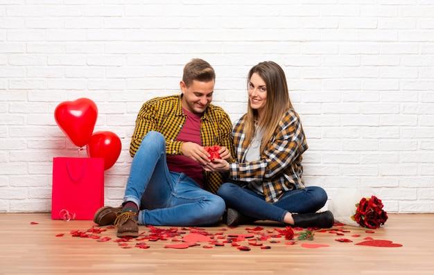 Coppie nel giorno di s. valentino al chiuso che tiene il contenitore di regalo