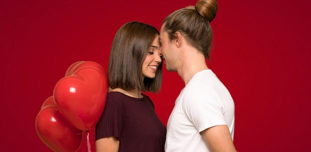 Coppie nel giorno di s. valentino che tiene un simbolo del cuore e palloni sopra fondo rosso