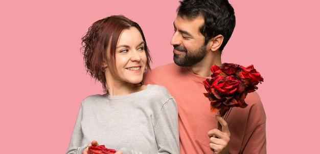 Coppie nel giorno di s. valentino con i fiori ed i regali sopra fondo rosa isolato