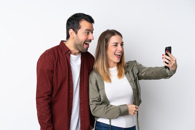 Coppie nel giorno di s. valentino sopra la parete isolata che fa un selfie con il cellulare