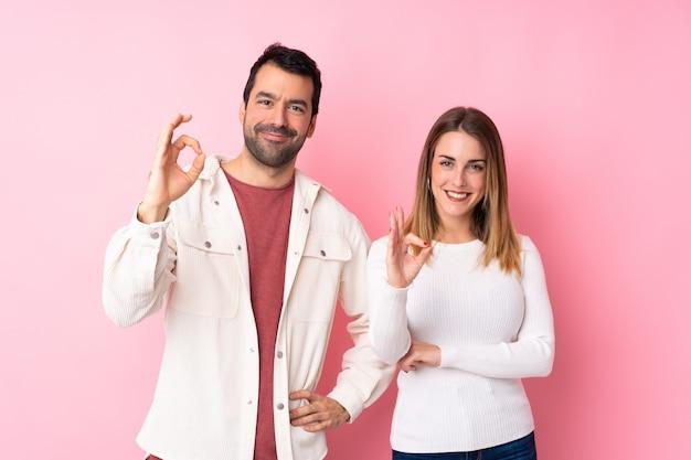 Coppie nel giorno di s. valentino sopra la parete rosa isolata che mostra un segno giusto con le dita