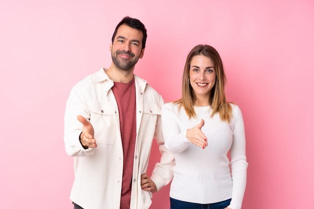 Coppie nel giorno di s. valentino sopra la parete rosa isolata che stringe le mani per la chiusura molto
