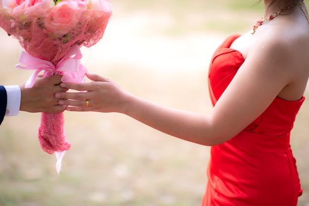 Coppie nell'amore che si tiene per mano insieme su all'aperto