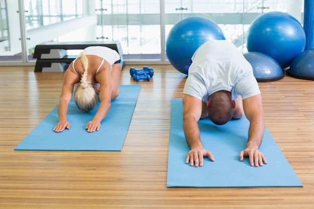 Coppie nella postura di piegamento allo studio di forma fisica