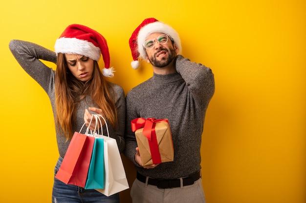 Coppie o amici che tengono i regali e borse della spesa che soffrono dolore al collo