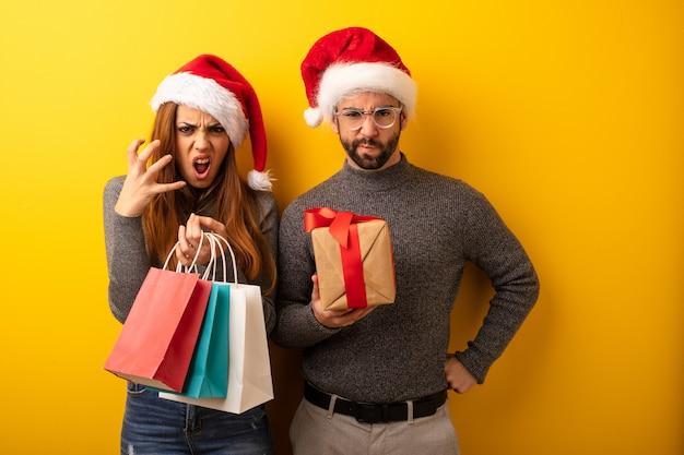 Coppie o amici che tengono i regali e sacchetti della spesa arrabbiati e turbati