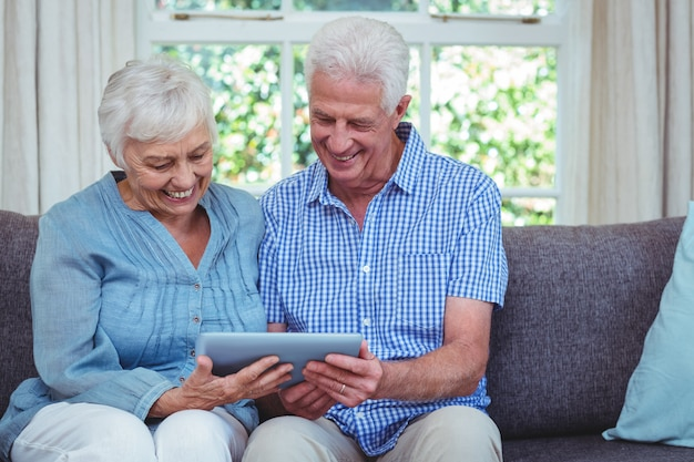 Coppie pensionate sorridenti facendo uso della compressa