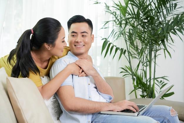 Coppie rilassanti nell'amore sullo strato con il computer portatile