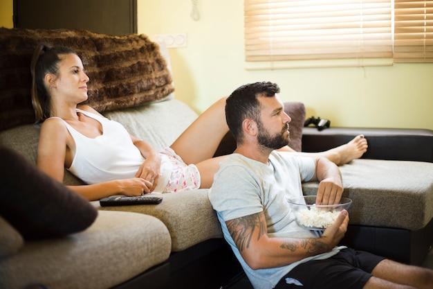 Coppie rilassate che guardano televisione a casa