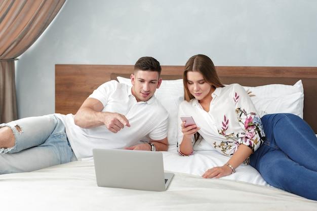 Coppie rilassate che lavorano a letto