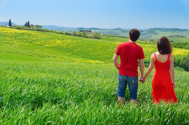 Coppie romantiche all'aperto divertendosi e camminando sul campo verde