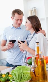Coppie romantiche che bevono vino mentre cucinando