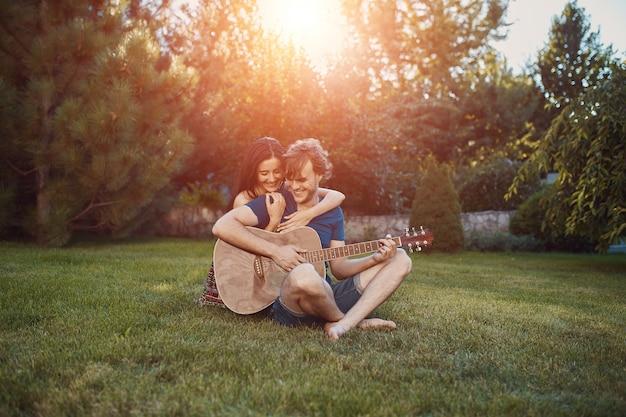 Coppie romantiche che si siedono sull'erba nel giardino