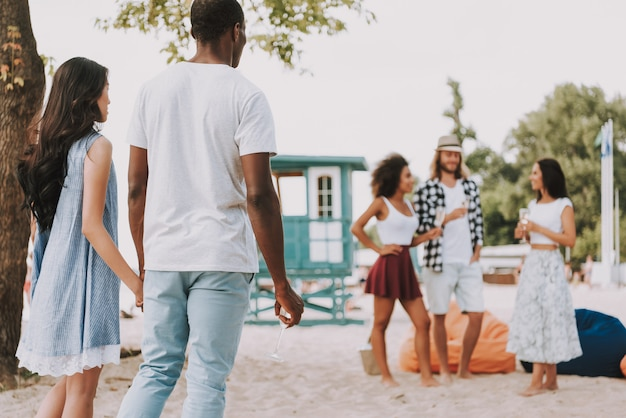 Coppie romantiche degli amici multirazziali del partito della spiaggia