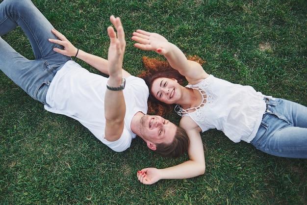 Coppie romantiche dei giovani che si trovano sull'erba in parco.