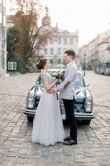 Coppie romantiche di nozze che stanno davanti alla retro automobile nera, bei sposa e sposo felici di estate, vecchie costruzioni della città sui precedenti