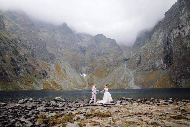 Coppie romantiche di nozze nella condizione di amore del lago sea eye in polonia. monti tatra.