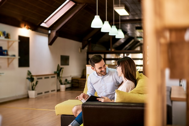 Coppie romantiche sorridenti che leggono insieme, dallo stesso libro.