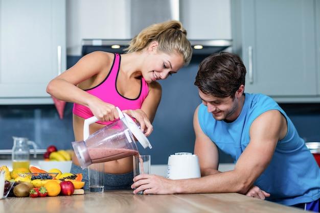 Coppie sane che preparano un frullato in cucina