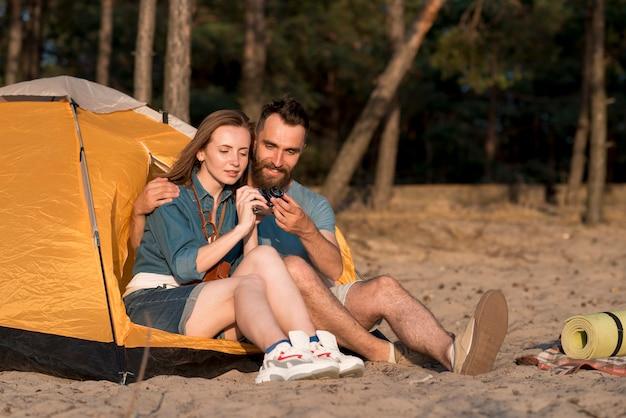 Coppie sedute che installano una macchina fotografica da una tenda