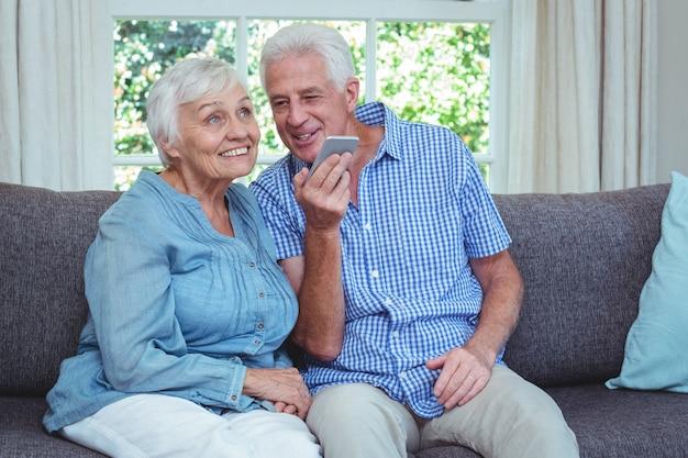 Coppie senior allegre che ascoltano la musica tramite il telefono