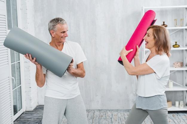 Coppie senior amorose che combattono con la stuoia rotolata di yoga a casa