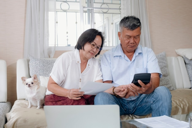 Coppie senior asiatiche che fanno e che calcolano le finanze domestiche.