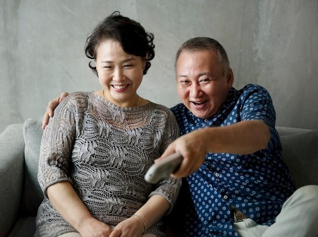 Coppie senior asiatiche che si siedono insieme al sofà