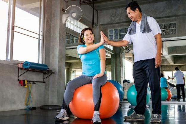 Coppie senior asiatiche che sorridono in abiti sportivi che si esercitano alla palestra.