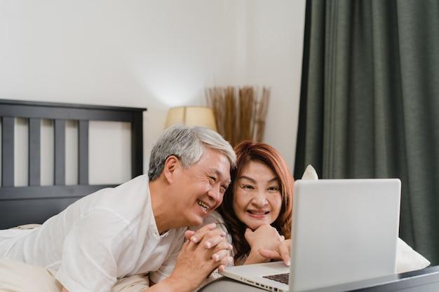 Coppie senior asiatiche facendo uso del computer portatile a casa. i nonni, il marito e la moglie cinesi senior asiatici felici dopo svegliano, guardando il film che si trova sul letto in concetto della camera da letto a casa di mattina.