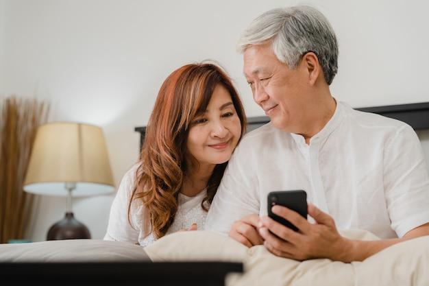 Coppie senior asiatiche facendo uso del telefono cellulare a casa. i nonni, il marito e la moglie cinesi senior asiatici felici dopo svegliano, guardando il film che si trova sul letto in concetto della camera da letto a casa di mattina.