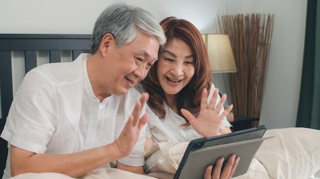 Coppie senior asiatiche facendo uso della compressa a casa. i nonni cinesi senior asiatici, la videochiamata che parla con il nipote della famiglia scherza mentre si trovano sul letto in concetto della camera da letto a casa di mattina.