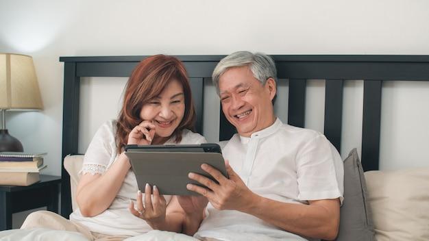Coppie senior asiatiche facendo uso della compressa a casa. i nonni, il marito e la moglie cinesi senior asiatici felici dopo svegliano, guardando il film che si trova sul letto in concetto della camera da letto a casa di mattina.