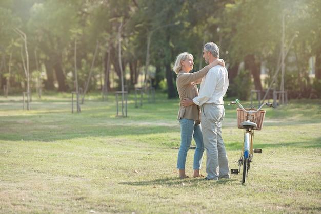 Coppie senior attive allegre con la bicicletta che camminano insieme attraverso il parco. attività perfette per le persone anziane in età pensionabile.