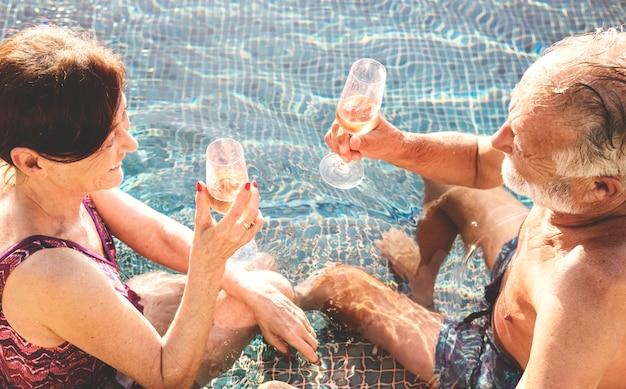 Coppie senior che bevono prosecco in una piscina