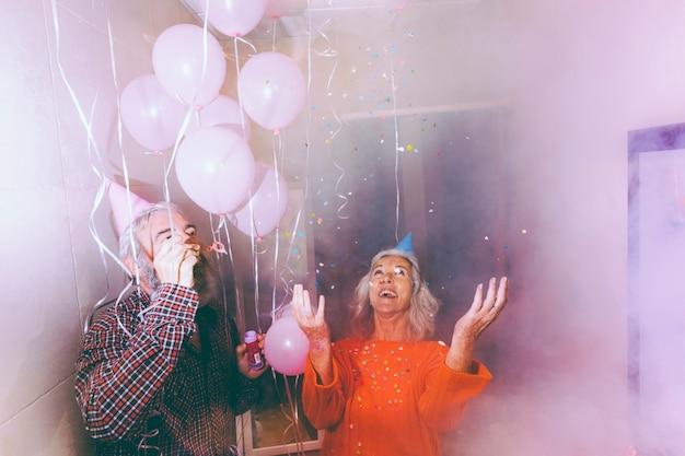 Coppie senior che celebrano insieme la coppia nella stanza fumosa decorata con palloncini rosa