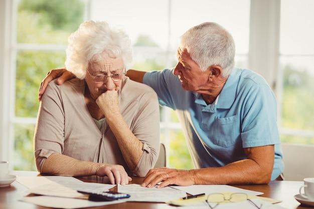 Coppie senior che contano le fatture a casa