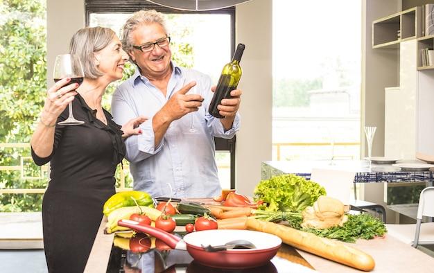 Coppie senior che cucinano alimento sano e che bevono vino rosso alla cucina della casa