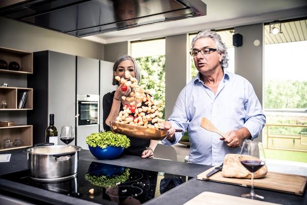 Coppie senior che cucinano e che si divertono nella cucina