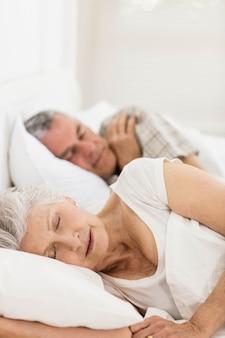 Coppie senior che dormono a letto a casa