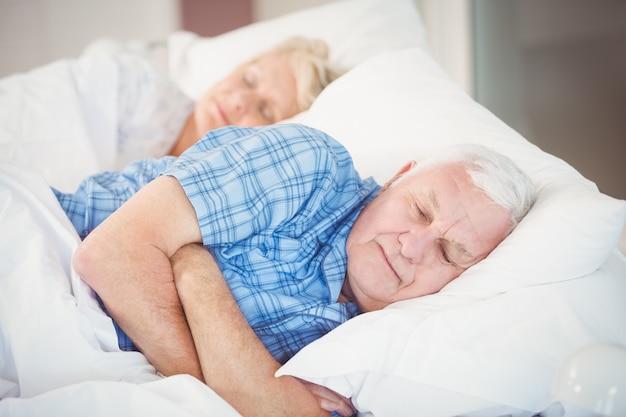 Coppie senior che dormono sul letto
