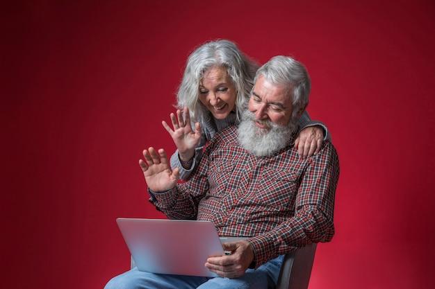 Coppie senior che esaminano computer portatile e che ondeggiano le loro mani contro il fondo rosso